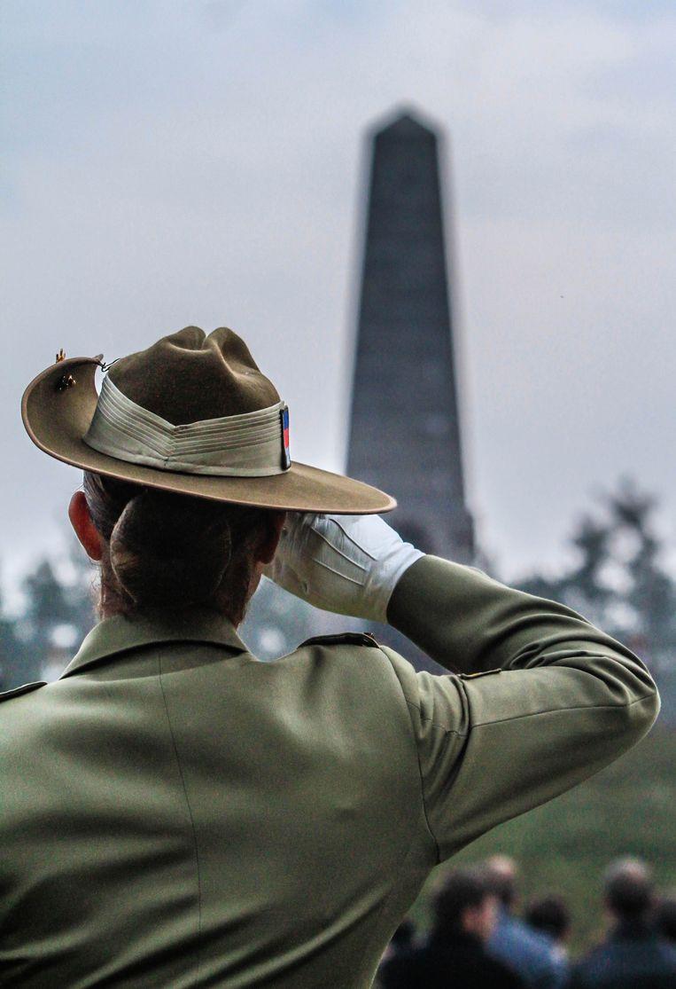 Een Australische militair groet het monument aan Buttes New British Cemetery.