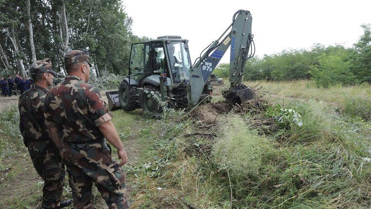 Hongaarse militairen prepareren de grond waar het hek moet komen. Beeld epa