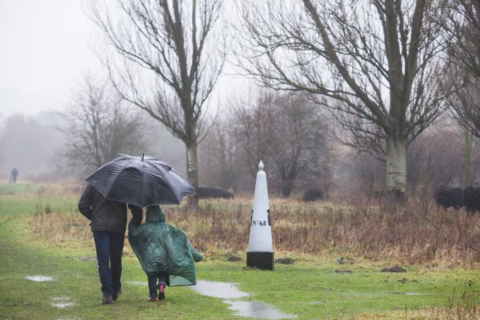 Een grenspaal markeert de overgang van Nederland naar België. De paal moet nog verplaatst worden.