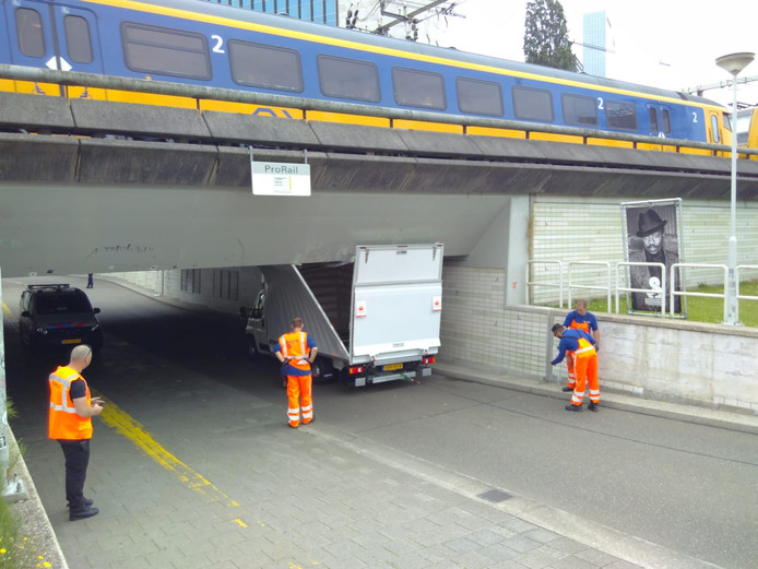 De vrachtwagen zit muurvast onder het spoorviaduct bij de Raampoortstraat.