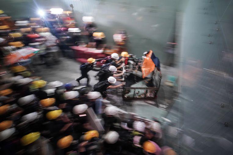 Protestanten bestormen de glazen pui van het parlementsgebouw met een container. Beeld Ivan Shum / Getty Images