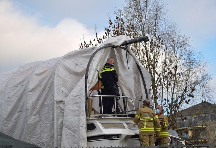 De politie en brandweer overleggen over hoe ze de inbreker naar beneden krijgen.