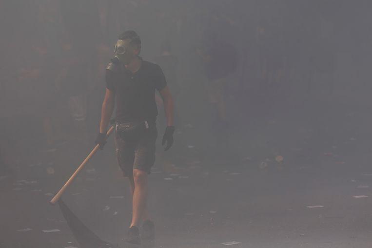 Een protestant loopt in een wolk van traangas tijdens de confrontaties die volgden op de uitspraak van een Griekse rechtbank.  Beeld EPA