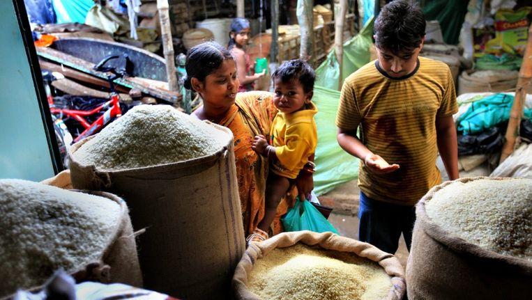 Een Indiase familie koopt rijst op een markt in Calcutta. Beeld epa