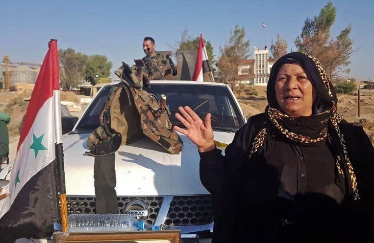 Op een foto verspreid door het Syrische staatspersbureau is te zien hoe het troepen van het regime welkom worden geheten in Tal Tamr, een plaatsje in het noordoosten van het land.  Beeld AFP
