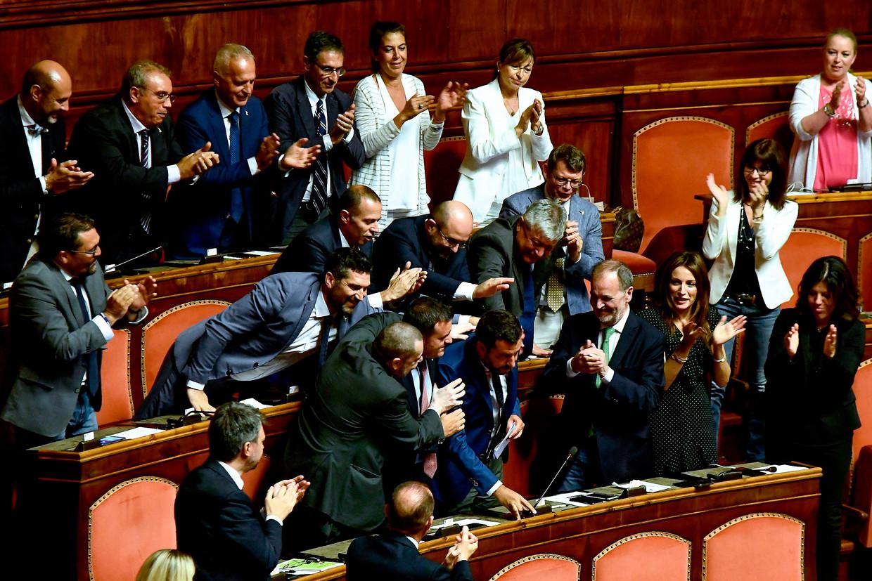 Vicepremier Matteo Salvini wordt gefeliciteerd door zijn partijgenoten tijdens het debat waarin hij een motie van wantrouwen indiende tegen zijn eigen regering. Beeld AFP