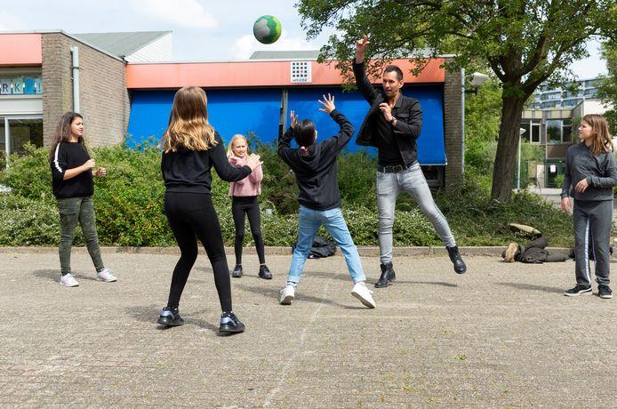 Op de Prinses Amaliaschool spelen leerlingen van groep 8, nadat ze weken thuis zijn geweest, in de pauze weer buiten op het plein.