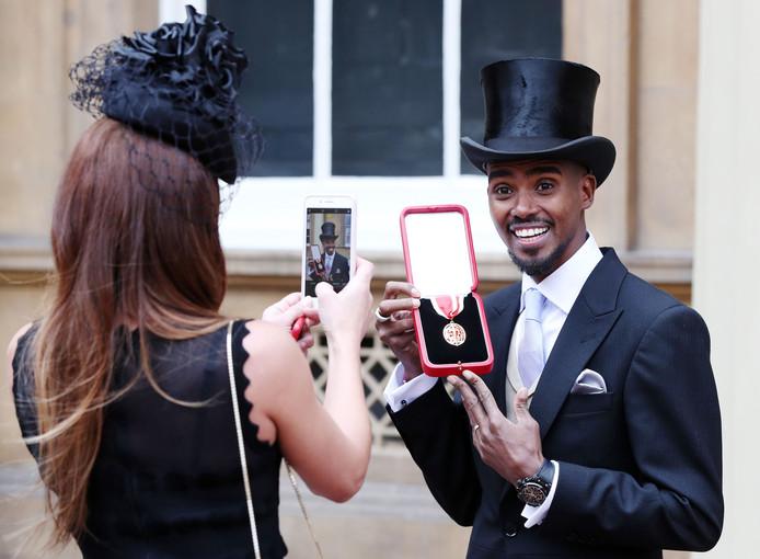 De Britse atleet Mo Farah wordt door zijn vrouw Tania gefotografeerd nadat hij tot ridder is geslagen in Buckingham Palace in London. Mo won twee gouden medailles bij de Olympische Spelen in 2016 op de 5 en 10 km. Foto Jonathan Brady