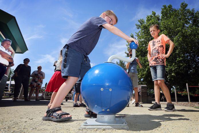 Kinderen in speeltuin 'de Hoge Neer' testen de nieuwe muziekbol die officieel in gebruik is genomen door jeugdburgemeester Danu Acs (rechts) en wethouder Frank Vrolijk (links).