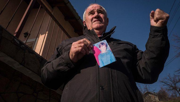 Ramiz Holjan met een foto van zoon Admir, omgekomen bij de beschietingen in Sarajevo in 1992. Beeld Nicola Zolin