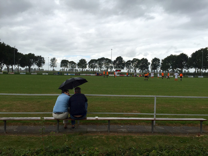 De supporters bij Avios/DBV-DSZ kijken onder de paraplu naar de wedstrijd. Foto: Raphael Drent