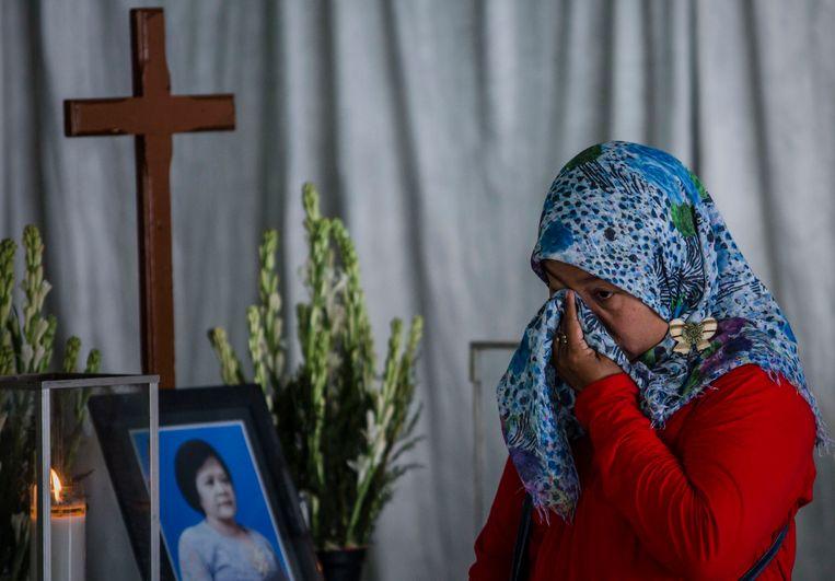 Yuliastuti rouwt bij de kist van Sri Puji, een van de slachtoffers van de aanslagen op drie kerken in Surabaya. Beeld Getty Images