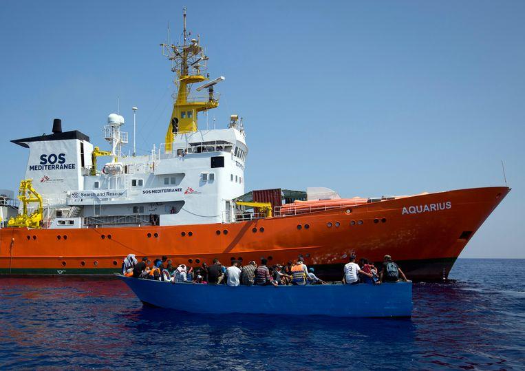 Migranten in een houten bootje naast de Aquarius in de Middellandse Zee. Archieffoto van augustus vorig jaar.
