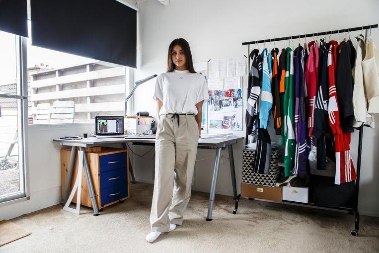 Daniëlle Cathari van der Voort, in haar zolderkamer in Purmerend. Aan het rek hangt de collectie waarmee ze debuteerde op de Fashion Week in New York Beeld Carly Wollaert
