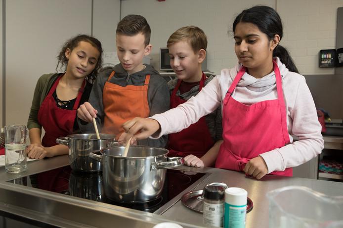 Leerlingen aan de slag in de leerlingenkeuken van de Capellenborg. Bij het clusteren van basisscholen op centrale plekken kunnen er meer voorzieningen komen, stelt een werkgroep in Olst-Wijhe.