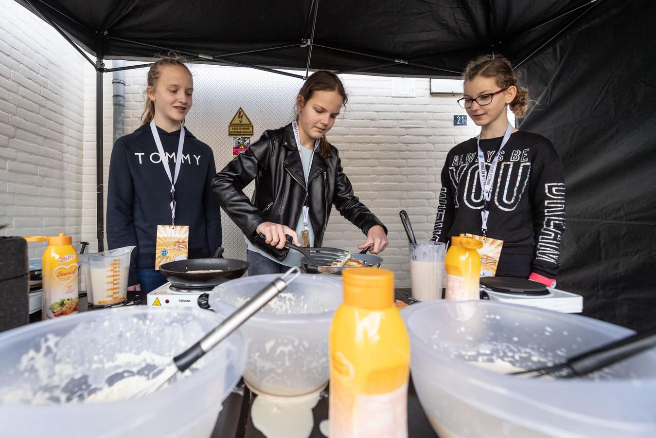 In het kader van NLdoet bakken jongeren in de wijk Wierden West pannenkoeken voor de buurt. (L-R) Iris, Milou en Milou druk aan het bakken.