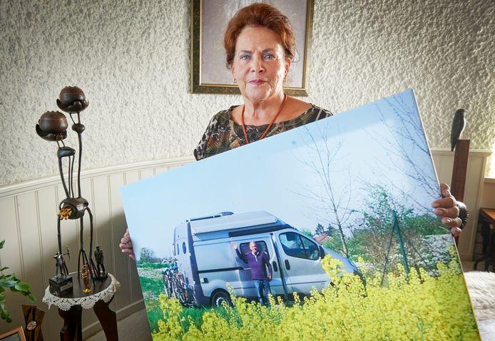 Yvonne van Loon met een foto van partner Sjef voor de camper waarmee ze graag op reis gingen. Links een kunstwerk ter herinnering aan de drie mannen die ze verloor, volgens haar idee gemaakt door een vriendin, met kleine urnen voor wat as en zonnestralen erin verwerkt.