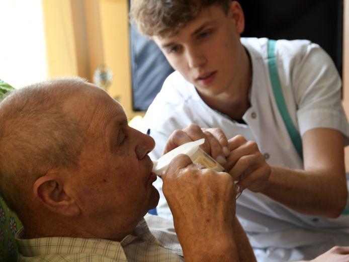 Meneer De Smit wordt geholpen met zijn koffie door Maxime Casier uit Assenbroek.