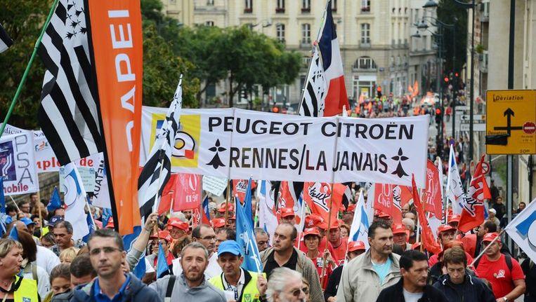 Franse werknemers van Peugoet Citroën protesteren tegen de massa-ontslagen in een fabriek bij Rennes, half september. Beeld AFP