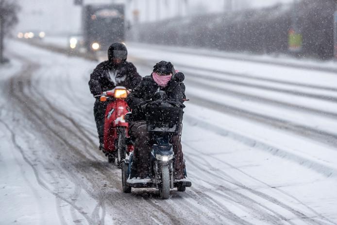 Een scootmobiel op weg onder winterse omstandigheden.