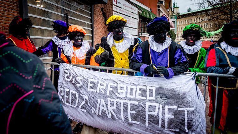Actievoerders voor het behoud van Zwarte Piet met een spandoek 'ons erfgoed, red zwarte piet' tijdens de intocht van Sinterklaas in Leiden. Beeld anp