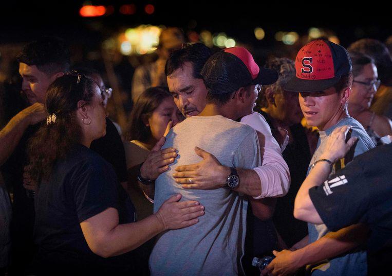 Familieleden van slachtoffers in El Paso tijdens een wake met kaarsen maandag.  Beeld AFP
