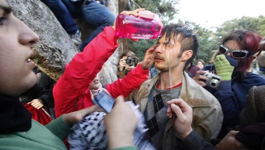Occupyer David Buscho wordt geholpen om de pepperspray uit zijn ogen te krijgen.