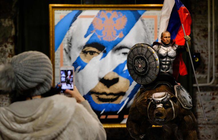 Op de dag dat president Poetin zijn kandidatuur bekendmaakte, opende de tentoonstelling 'Superpoetin' in het Umam-museum in Moskou. De kunstenaars die Poetin onder meer afbeelden als superheld en Romeinse keizer, kregen de opdracht de populariteit van Poetin weer te geven. Beeld AFP