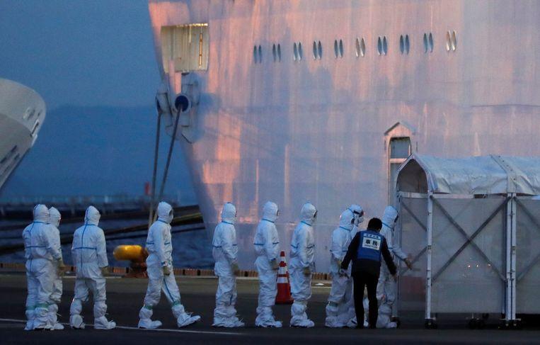 Gezondheidsmedewerkers in beschermende pakken gaan aan boord van de Princess Diamond.