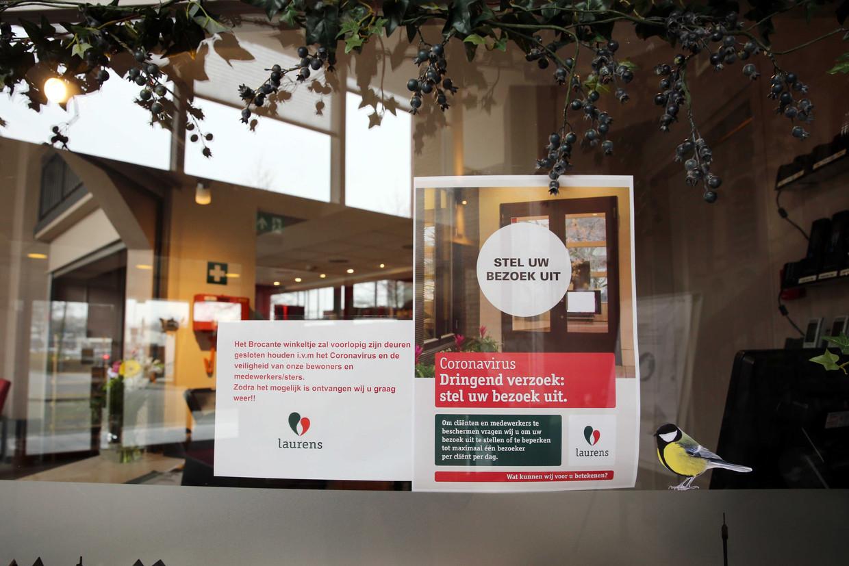 Een aankondiging op de deur van een verpleeghuis om bezoek te beperken