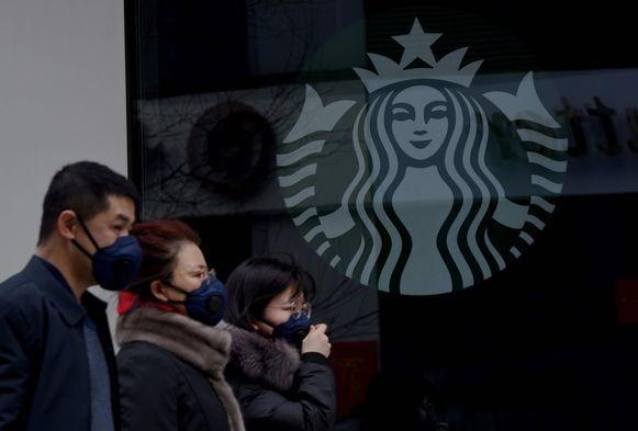Mensen met mondmaskertjes passeren voorbij een vestiging van Starbucks in Peking.
