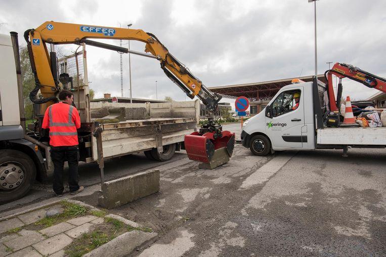 De technische dienstvan Poperinge plaatst betonblokken rond de parking.
