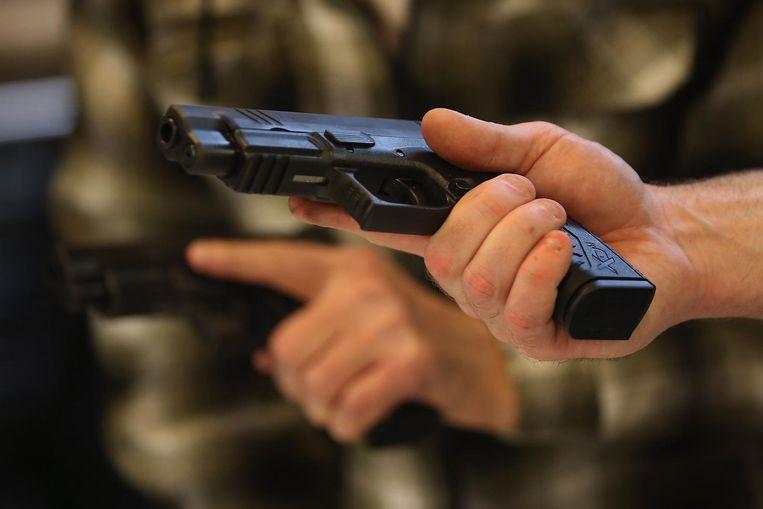 Een student leert tijdens een cursus van de NRA in Tinley Park, in de staat Illinois, hoe je een wapen moet vasthouden. Wie een handwapen in de VS wil kopen, moet ten minste 21 jaar zijn. Beeld AFP