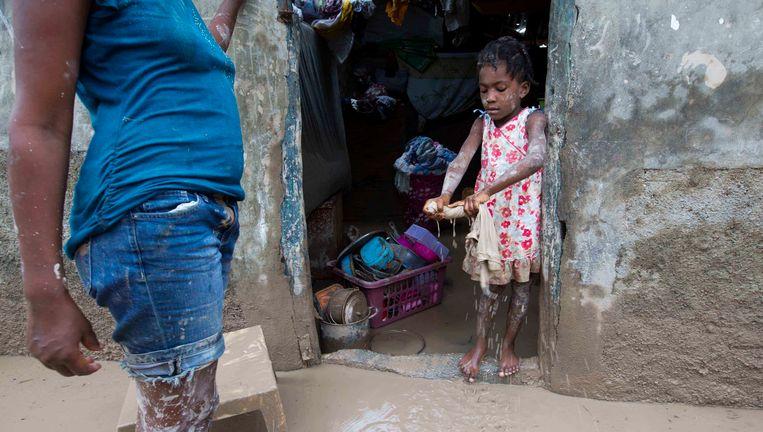 Een meisje in Haïti helpt haar moeder om modder uit hun huis te dweilen, na verwoestingen en overstromingen veroorzaakt door de orkaan Matthew. Beeld AP