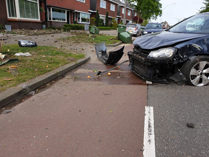 De weg ligt bezaaid met brokstukken van de auto en met groenafval.