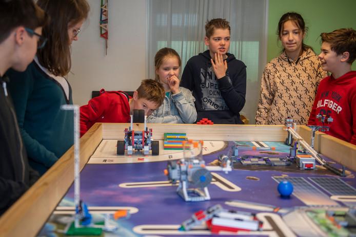 Bedrukte gezichten bij de deelnemers aan de FIRST LEGO League. Doet robot Starbot wel wat hem is opgedragen?