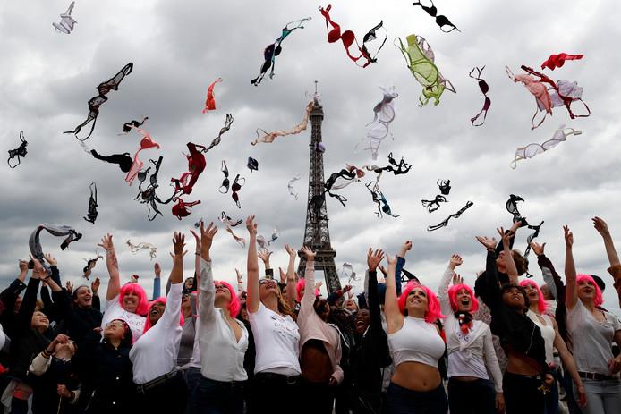 Tientallen vrouwen gooien hun beha's in de lucht als onderdeel van de jaarlijkse 'Pink Bra Toss' voor de Eiffeltoren. Het evenement georganiseerd door Pink Bazaar heeft tot doel het bewustzijn van borstkanker te vergroten. Foto  Christophe Ena