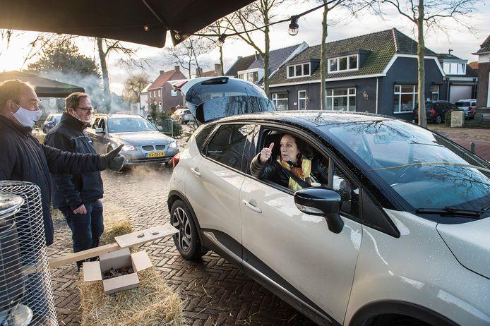 Automobilisten pakken een sleutelhanger van het plankje. De achterklep staat open, zodat de kerstboom uit de achterbak kan worden gehaald.