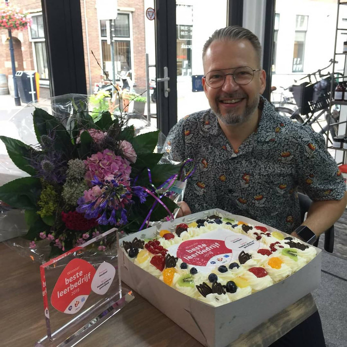 Frank Vonkeman met oorkonde en taart die bij de prijs horen.