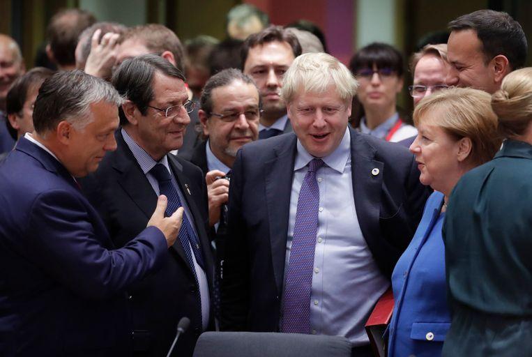 Een opgeluchte Boris Johnson wordt op de Europese top omringd door Hongaars premier Viktor Orban, Cypriotisch president Nicos Anastasiades,  Iers premier Leo Varadkar en de Duitse bondskanselier Angela Merkel. Is morgen hem het lachen vergaan?