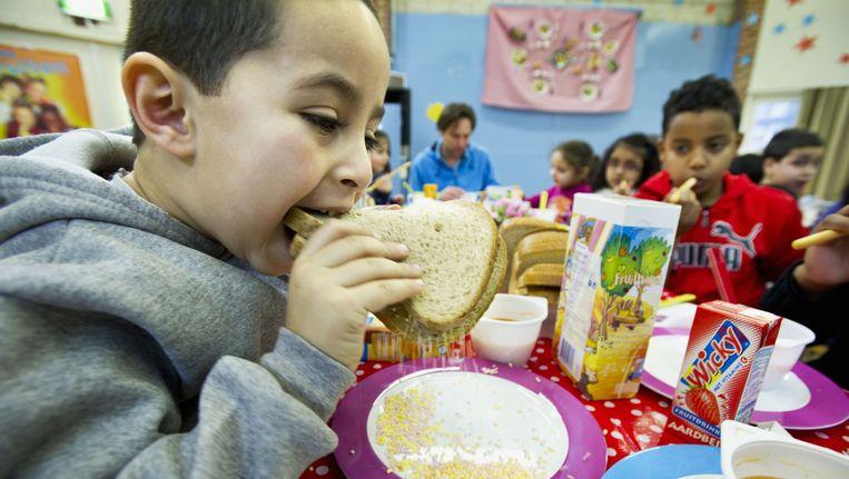 Leerlingen eten samen op een basisschool Spaarndammerhout in Amsterdam. Beeld anp