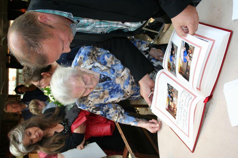 De 105-jarige tekent het guldenboek van de gemeente