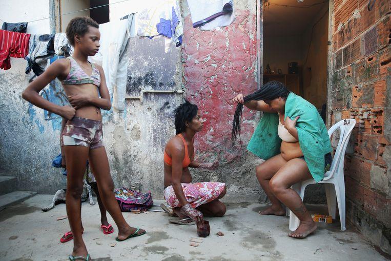 Een ontvanger (rechts) in Rio de Janeiro van Bolsa Familia, een soort basisinkomen waarmee Brazilië de toon zette. Beeld Getty