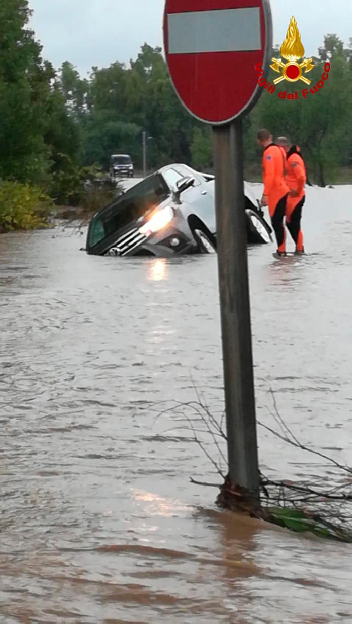 Een auto wordt meegesleurd door het water.