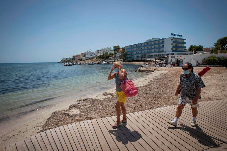 Toeristen met mondmaskers op het strand van Ibiza. De Spaanse toeristensector krijgt harde klappen vanwege de gevolgen van het coronavirus. Beeld AFP