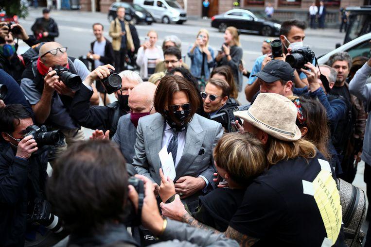 Johnny Depp (midden, in het grijze pak) wordt belaagd door pers en fans bij de rechtbank in Londen.