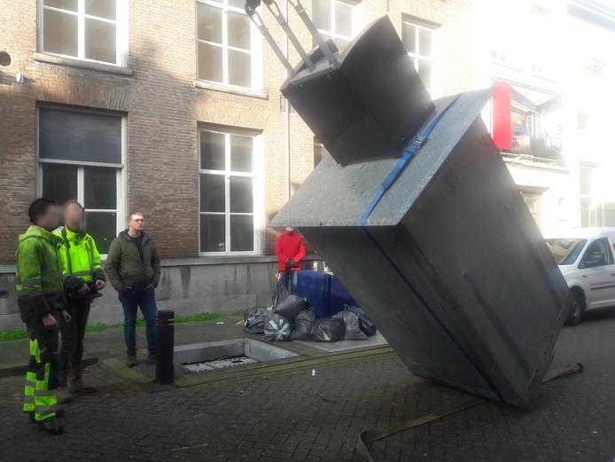 De gevallen container in Den Bosch wordt overeind gehesen om alsnog leeg te worden gemaakt.