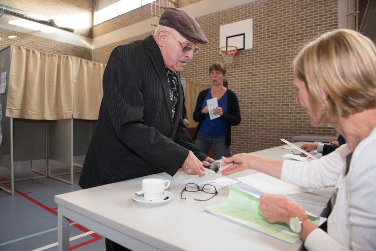 Een kiezer geeft zijn identiteitskaart af om te kunnen stemmen.