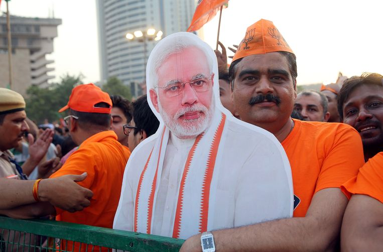 Een aanhanger van de Bhartya Janta Party (BJP) met een poster van premier Narendra Modi. Beeld EPA
