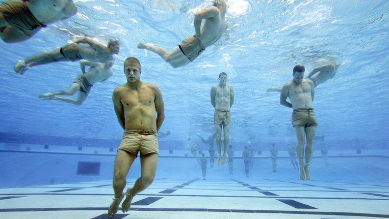 Een onderdeel van de basistraining tot Navy SEAL is het zogenoemde drownproofing. Daarbij moet de militair, aan handen en voeten gebonden, 20 minuten op en neer naar de bodem van het zwembad dobberen, 5 minuten blijven drijven, een stuk zwemmen, onder water een voorwaartse en achterwaartse koprol maken en met de tanden een duikbril van de bodem pakken. Wie de bodem raakt, kan naar huis. Beeld